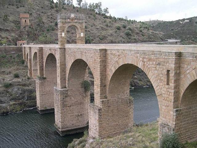 Красивая архитектура Алькантара, арки по бокам, которые являются основными и большая арка посредине, имеющая декоративное предназначение.